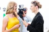 Reporter and cameraman shoot an interview