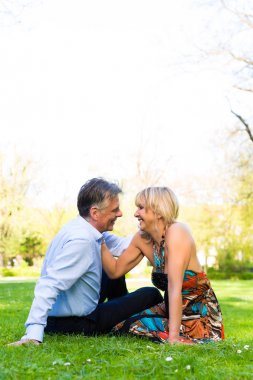 Senior couple during spring on a meadow in the city