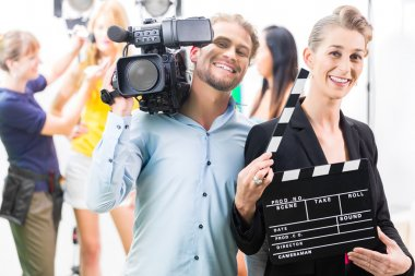 Production team with camera and take clap on film set or studio