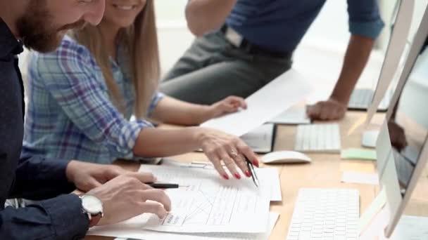 zaměstnanci diskutující finanční dokumenty na schůzce kanceláře.