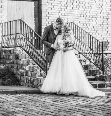 bride and groom kiss, standing on the porch of the house