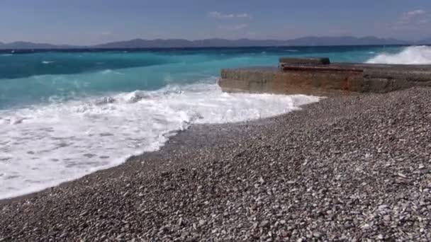 Vlny zřítilo na oblázkové pobřeží s molem