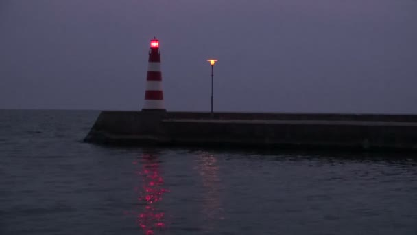 Sea lighthouse and pier at night