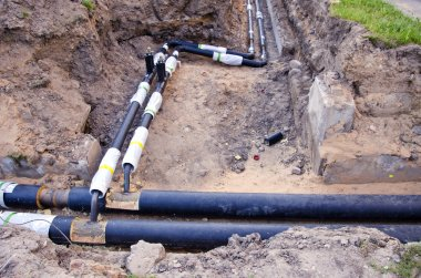 plastic modern technology black heating pipes in trench near house