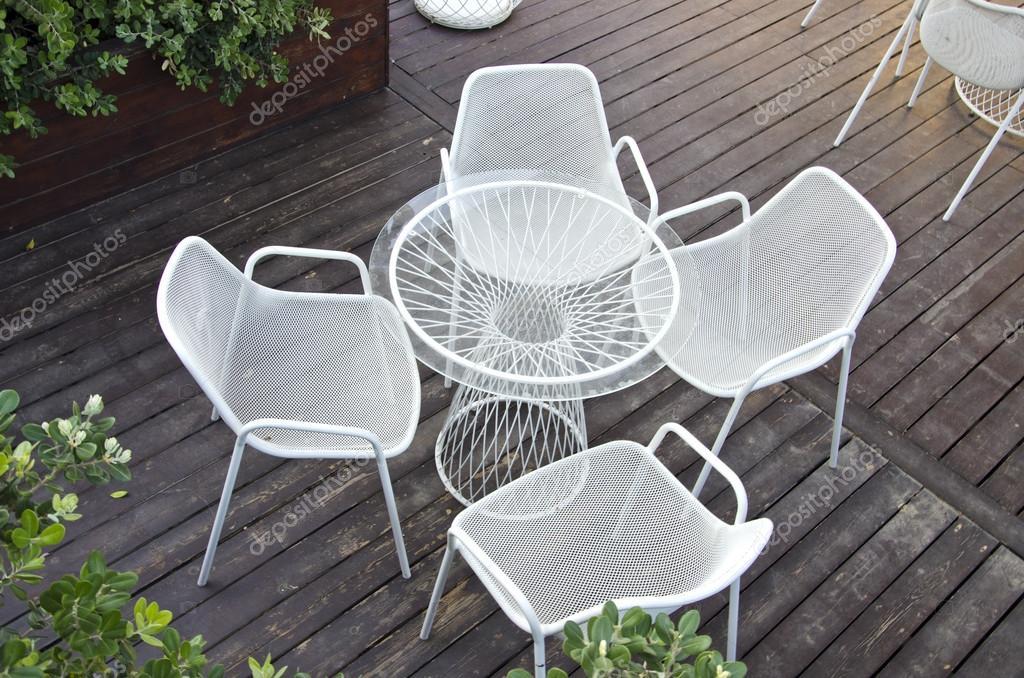 Glazen tafel met vier stoelen in buitenshuis tuin u stockfoto