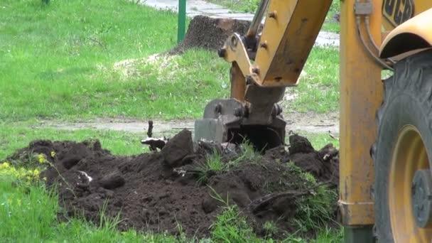 průmyslové rypadlo kopání díry na trávníku