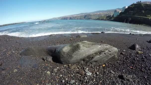 Pohled na černé písečné pláže s rockem oceánem, časová prodleva 4k