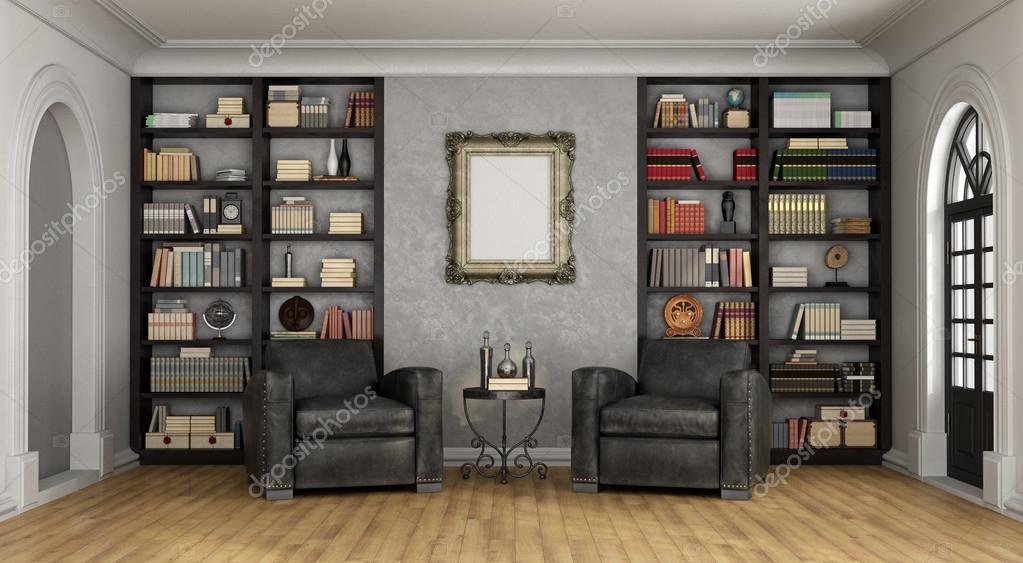 luxe woonkamer met grote boekenkast en fauteuils stockfoto