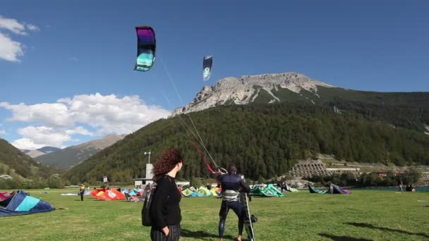 Woman looking at kitesurf sails lying on a meadow