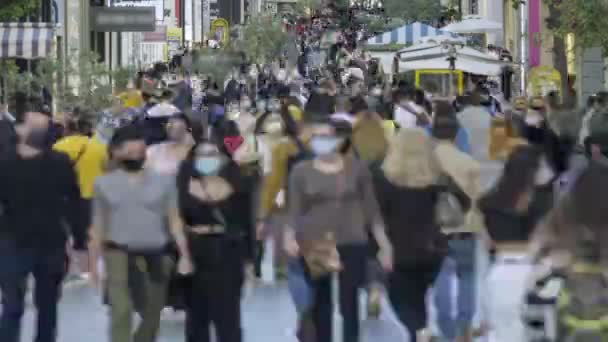 time lapse of crowd goes up and down a busy shopping street wearing a protective mask for covid19