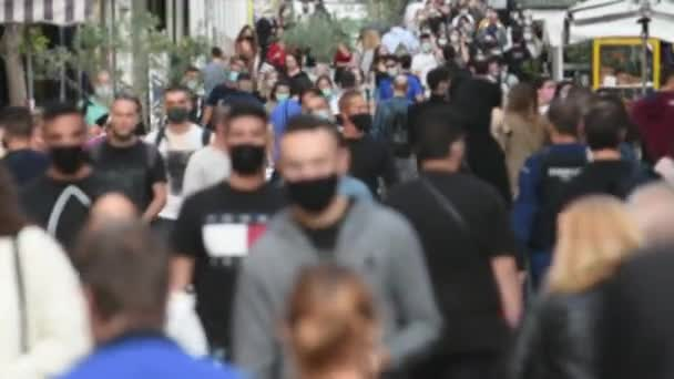 video of a crowd goes up and down a busy shopping street wearing a protective mask for covid19