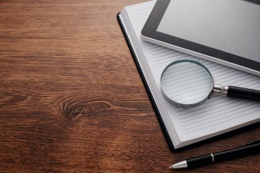 Tablet and Magnifying Glass on Notes at the Table