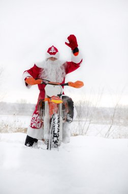 Santa Claus on a motorcycle with his hand raised motocross
