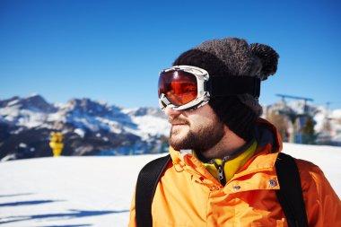 smiley skier in orange jacket and mask