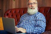 Mann sitzt mit Laptop am Fenster