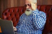 alter Mann sitzt auf Couch und arbeitet mit Laptop