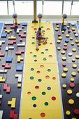 Sportovkyně na vrcholu zdi v lezecké centrum