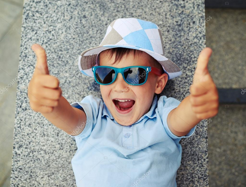 9635076ffa2f8 Small boy in sunglasses and hat is lying on the street stairs parapet and  giving thumbs up — Photo by ...