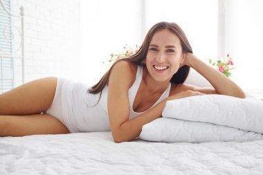 Sexy smiling woman in white underwear on white bed