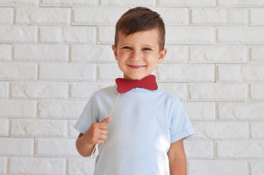 Adorable small boy holding a paper moustache on stick and smilin
