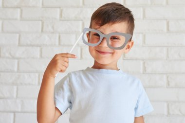 Curious and joyful boy holding paper glasses on a stick