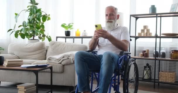 Behinderter alter Mann mit Handy im Rollstuhl sitzend