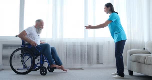 Krankenschwester ermutigt behinderte alte Patientin, aus dem Rollstuhl zu steigen