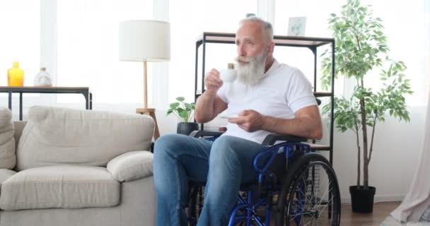 Alter Mann mit Behinderung trinkt Kaffee im Rollstuhl
