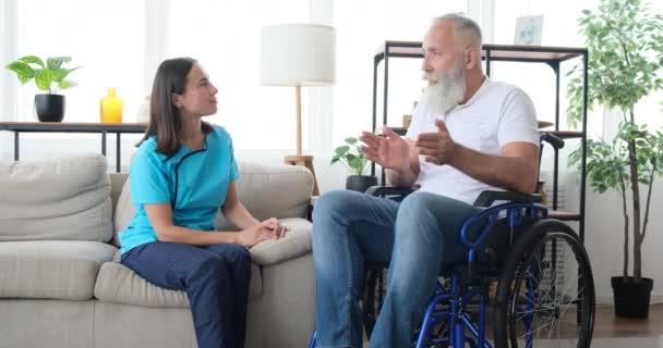 Krankenschwester spricht zu Hause mit älterer Patientin im Rollstuhl