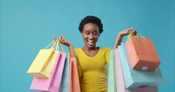 Žena tančí s nákupními taškami v rukou