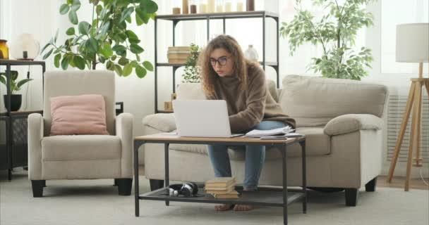 Frau benutzt Laptop und analysiert Dokument zu Hause