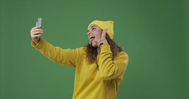 Woman taking selfie and photo messaging using mobile phone