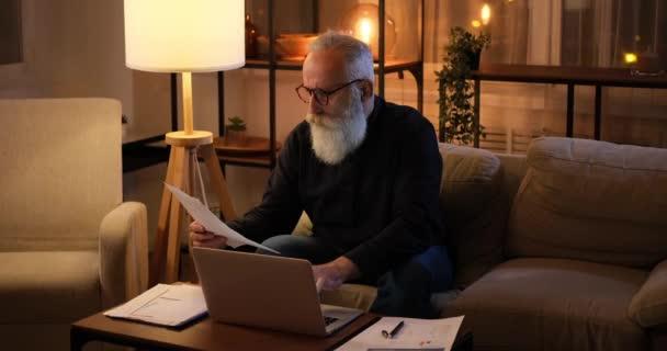 Alter Mann benutzt Laptop und analysiert spätabends Dokumente