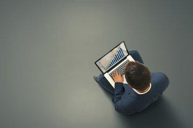 man sitting on the dark floor with laptop