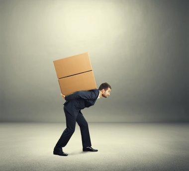 Tired young businessman carrying on the back two heavy boxes. photo in the grey room stock vector