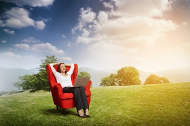 Relaxed woman with closed eyes sitting on the red chair with laptop on green meadow over hill and blue sky stock vector