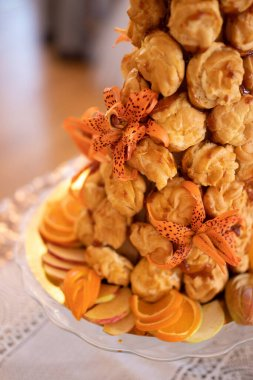Croquembouche, a classic French wedding cake, beautiful tower of tiny profiteroles also called choux. It is wrapped in delicious golden caramel and filled with a yummy creme patissiere