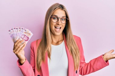Young blonde woman wearing business style holding mexican pesos celebrating achievement with happy smile and winner expression with raised hand