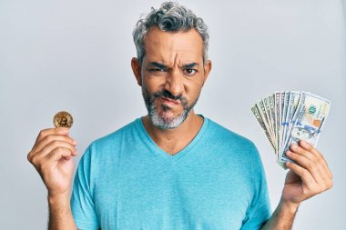 Middle age grey-haired man holding dollars and bitcoin skeptic and nervous, frowning upset because of problem. negative person.