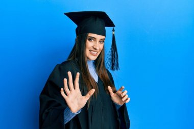 Beautiful brunette young woman wearing graduation cap and ceremony robe disgusted expression, displeased and fearful doing disgust face because aversion reaction. with hands raised