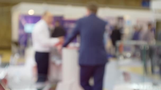 meeting of business people behind the counter in the large hall.blurry defocused video.business background