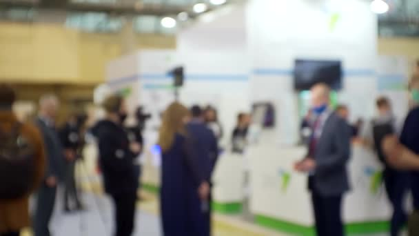 film crew interviews a businessman in a large bright hall.blurry defocused video about education or business