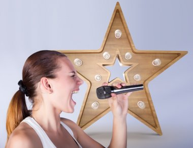 Girl with a microphone on the background of sign star.