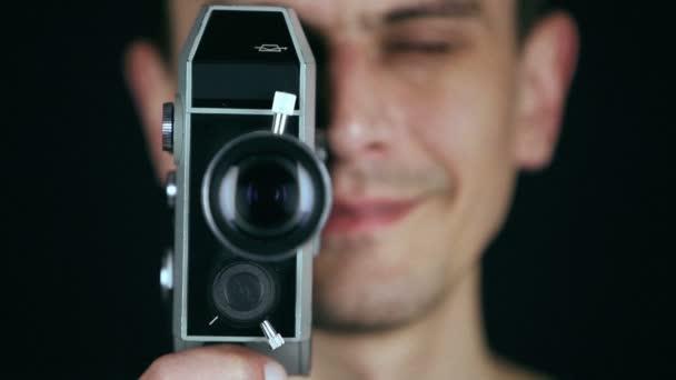 Fiatal felnőtt férfi retro film fényképezőgép használata, hogy a film a fekete háttér. Régi film hatását. HD
