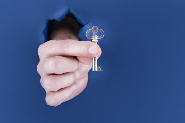 Male hand breaking through the blue paper background and holding key