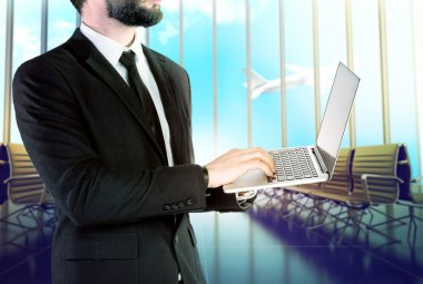 Businessman with digital notebook on blurred background airport .