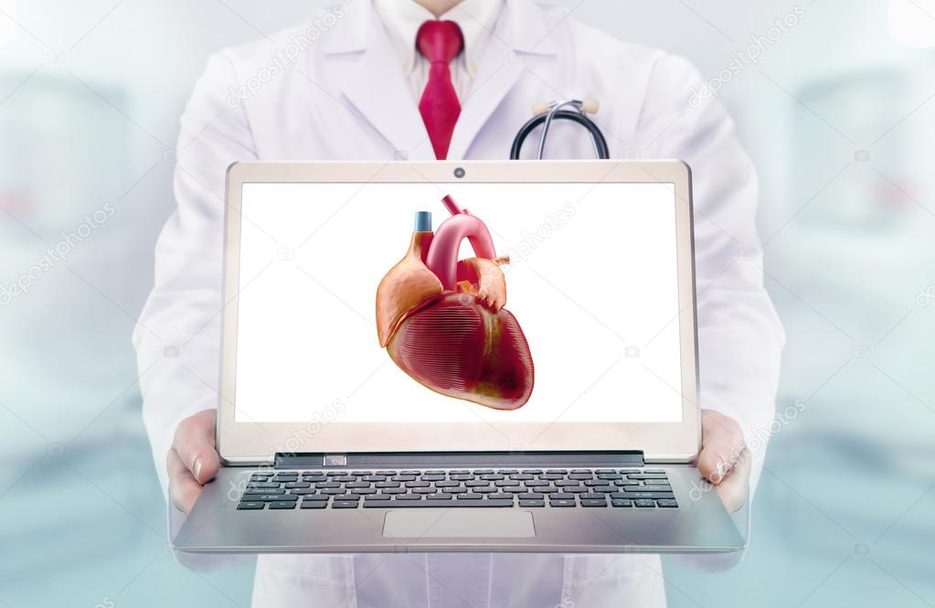 Doctor with stethoscope in a hospital. Heart on the laptop monitor ...
