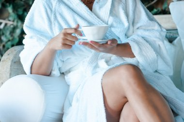 Young woman in a bathrobe with a cup of tea