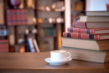 Stack of old books and cup with coffee over wooden table, retro filtered image