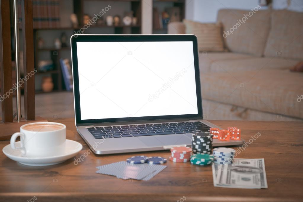 Poker set in a metallic case with laptop over wooden table, retro filtered image